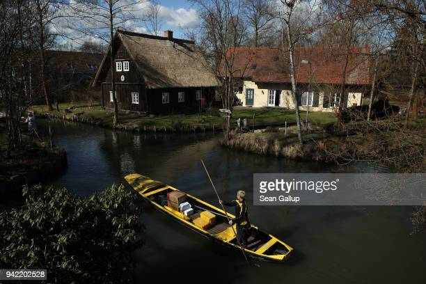 German postal carrier Deutsche Post postal worker Andrea Bunar guides her flat-bottomed canoe past houses as she delivers the mail in the web of...