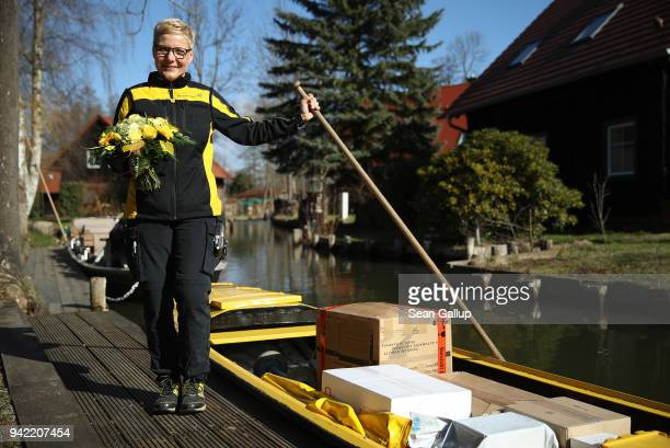 German postal carrier Deutsche Post postal worker Andrea Bunar pauses with flowers she received before venturing on the first day of her delivery...