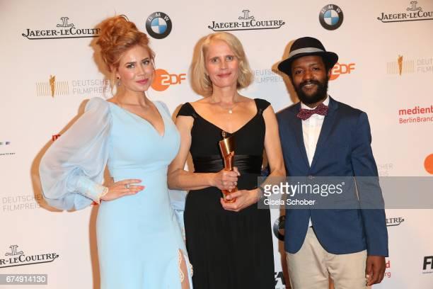 German presenter and laudator Palina Rojinski and award winner for best cut in 'Toni Erdmann' Heike Parplies and Eric Kabongo during the Lola German...