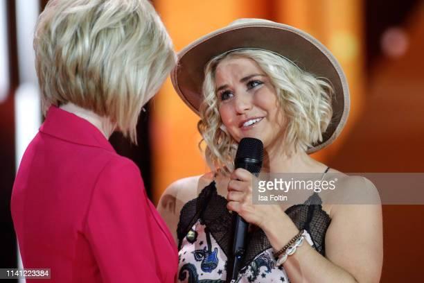 German presenter Carmen Nebel and Swiss singer Beatrice Egli speak onstage during the television show 'Willkommen bei Carmen Nebel' at Velodrom on...