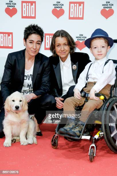 German presenter Dunja Hayali with an assistance dog puppy Vita founder Tatjana Kreidler and Robin Richter attend the 'Ein Herz fuer Kinder Gala' at...