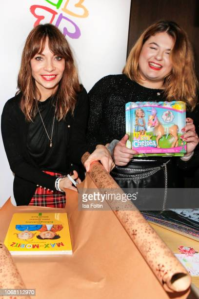 German presenter Jean Bork and German singer Alina Wichmann alias Alina wrap presents for children in need during the Laughing Hearts Charity...