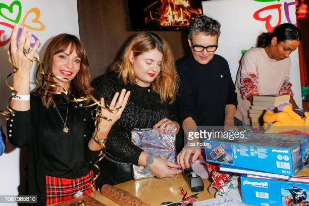 German presenter Jean Bork German singer Alina Wichmann alias Alina Rolf Scheider and German presenter Annabelle Mandeng wrap a present for children...