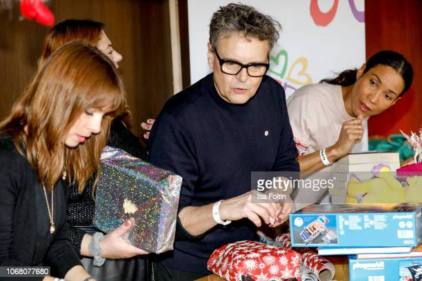 German presenter Jean Bork German singer Alina Wichmann alias Alina Rolf Scheider and German presenter Annabelle Mandeng wrap presents for children...