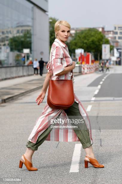 German presenter Susann Atwell wearing a brown bag by Stiebich & Rieth, brown sandals by Closed, olive green pants and a long red and white blouse by...