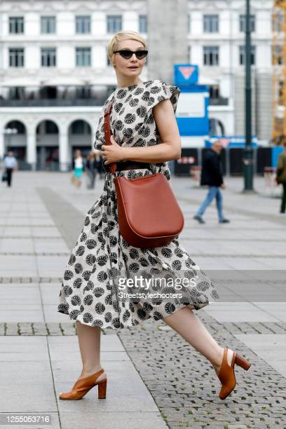 German presenter Susann Atwell wearing sunglasses by Bellevue, a brown bag by Stiebich & Rieth, a beige midi length dress with black pattern by SoSue...