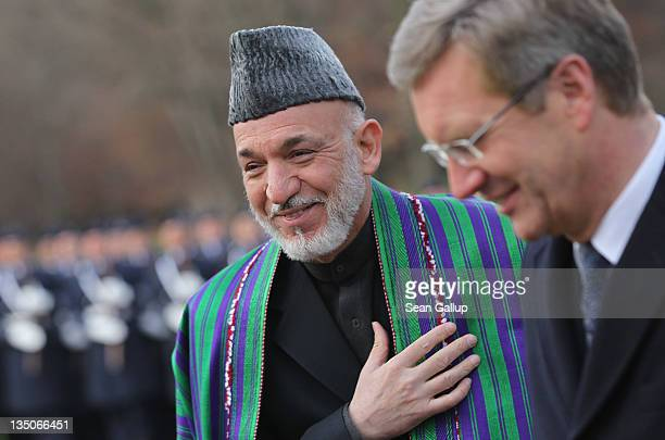 German President Christian Wulff and Afghan President Hamid Karzai finish reviewing a guard of honour upon Karzai's arrival at Bellevue Palace on...