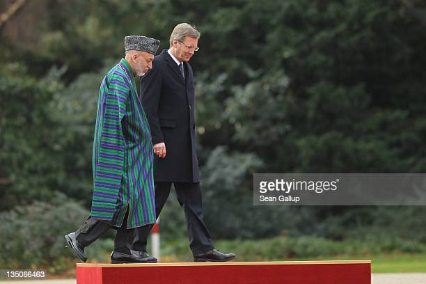 German President Christian Wulff and Afghan President Hamid Karzai prepare to review a guard of honour upon Karzai's arrival at Bellevue Palace on...