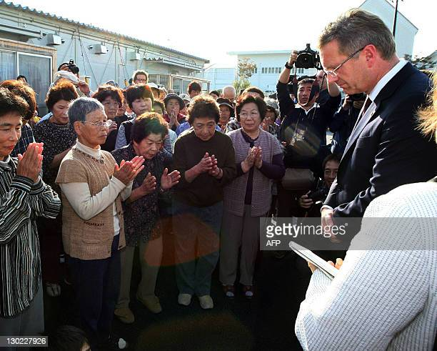German President Christian Wulff and evacuated people from their residences near stricken nuclear power plant pray for victims of the March 11...