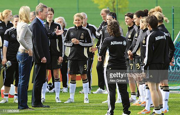 German President Christian Wulff and his wife Bettina talk to players of the German Women's national football team during a visit at their training...