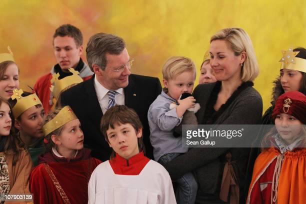 German President Christian Wulff and his wife Bettina, who is holding their son Linus pose with child Epiphany carolers at Bellevue Presidential...