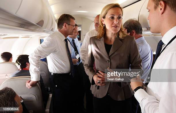 German President Christian Wulff and his wife First Lady Bettina Wulff speak to journalists while flying in a government plane to Switzerland on...
