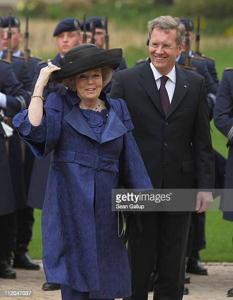 German President Christian Wulff and Queen Beatrix of the Netherlands review a guard of honor at Bellevue Presidential Palace on April 12, 2011 in...