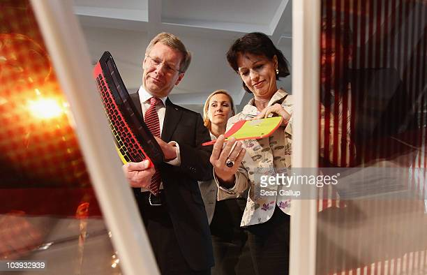German President Christian Wulff and Swiss President Doris Leuthard look at solarpowered computer keyboards behind pigmentbased solar cells as German...