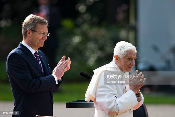 German President Christian Wulff applauds as Pope Benedict XVI waves to assembled guests in the gardens at Schloss Bellevue presidential palace on...