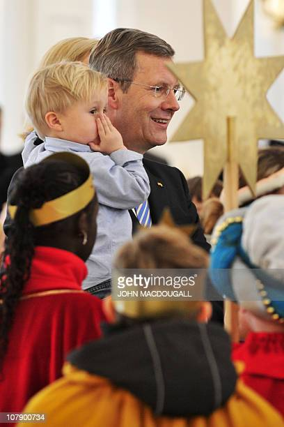 German President Christian Wulff , his wife Bettina and their two-year-old son Linus speak with Carol singers from the Hamburg area during a...
