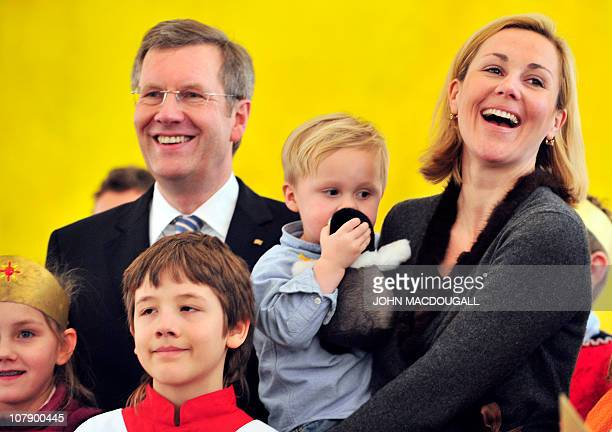 German President Christian Wulff , his wife Bettina Wulff and their two-year-old son Linus pose with Carol singers from the Hamburg area during a...