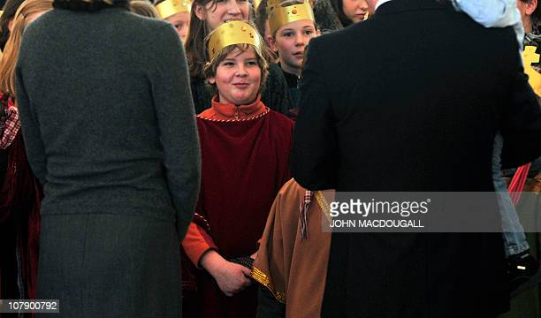 German President Christian Wulff holding their two-year-old son Linus and his wife Bettina speak with Carol singers from the Hamburg area during a...