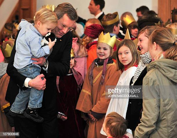 German President Christian Wulff holds his two-year-old son Linus as he speaks with carol singers from the Hamburg area during a reception at the...