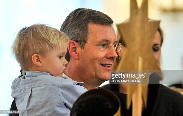 German President Christian Wulff holds his two-year-old son Linus as he and his wife Bettina Wulff speak with carol singers from the Hamburg area...