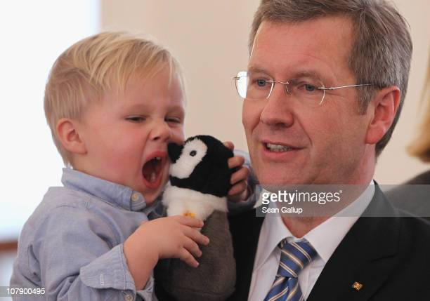 German President Christian Wulff holds his yawning son Linus while receiving child Epiphany carolers at Bellevue Presidential Palace on January 6,...