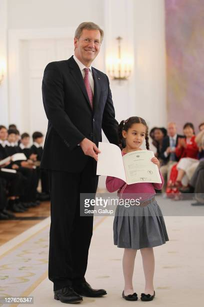 German President Christian Wulff presents young Palestinian Razan Faraj her German citizenship certificate during a ceremony for 22 new German...