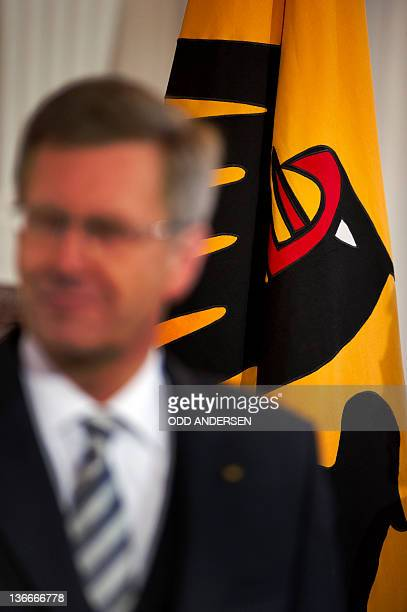 German President Christian Wulff stands in front of a flag during a greeting ceremony at Bellevue Palace in Berlin on January 10, 2012. The German...