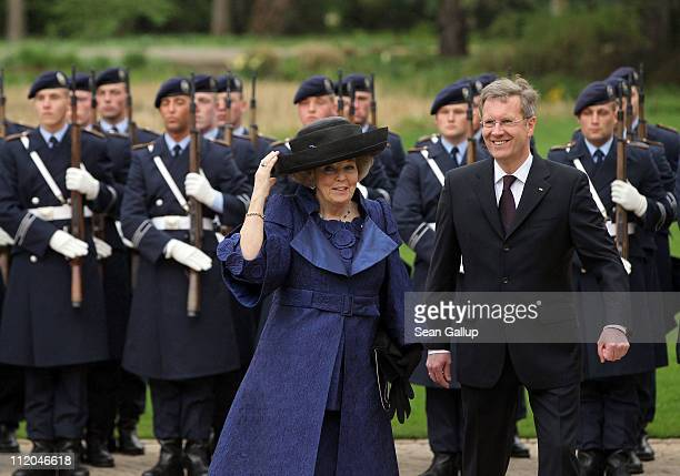 German President Christian Wulff welcomes Queen Beatrix of the Netherlands with the guard of honor at Bellevue Presidential Palace on April 12 2011...