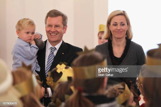 German President Christian Wulff, who is holding his son Linus and his wife Bettina receive child Epiphany carolers at Bellevue Presidential Palace...
