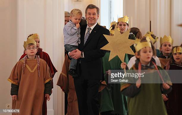 German President Christian Wulff, who is holding his son Linus receives child Epiphany carolers at Bellevue Presidential Palace on January 6, 2011 in...