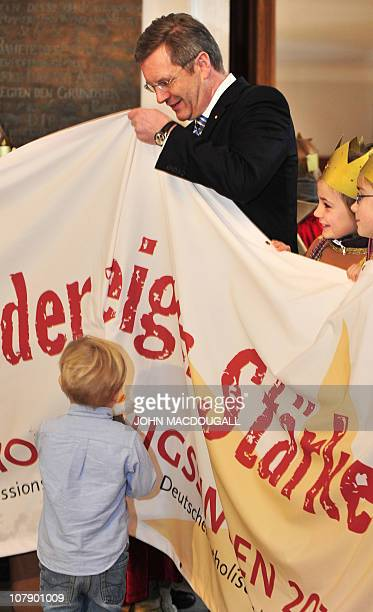 German President Christian Wulff wrestles with a banner as his two-year-old son Linus looks on during a reception for carol singers from the Hamburg...