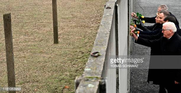 German President Frank-Walter Steinmeier and official guests place flowers at the Wall Memorial during the central commemoration ceremony for the...