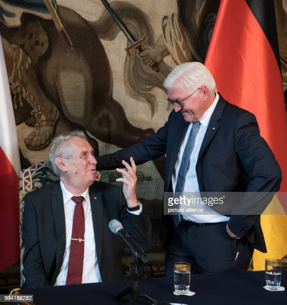 German President FrankWalter Steinmeier and the President of the Czech Republic Milo· Zeman talk to each other at the end of a press conference after...