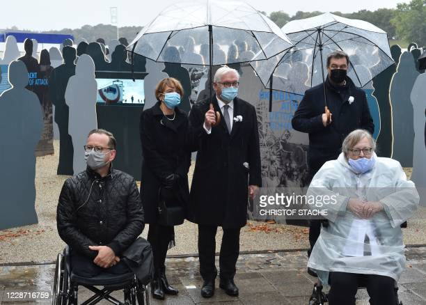 German President FrankWalter Steinmeier his wife Elke Buedenbender and Bavaria's State Premier Markus Soeder stand behind survivors of the...