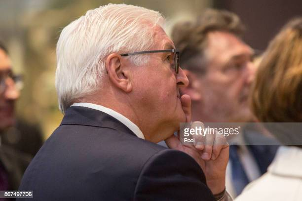 German President FrankWalter Steinmeier looks at the painting 'The Studio' by East German artist Bernhard Heisig during an opening tour at the...