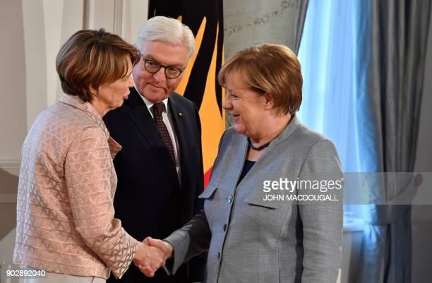 German President FrankWalter Steinmeier looks on as his wife Elke Buedenbender shakes hands with German Chancellor Angela Merkel during a New Year's...