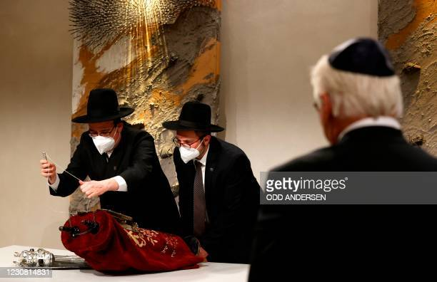German President Frank-Walter Steinmeier looks on as Rabbi Elias Dray and Rabbi Shaul Nekrich wrap the historic Sulzbach Torah Scroll from 1792 after...