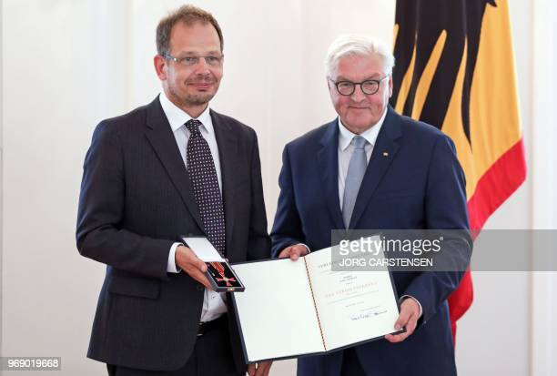 German President FrankWalter Steinmeier presents German sports journalist Hajo Seppelt with the Federal Cross of Merit for his outstanding commitment...