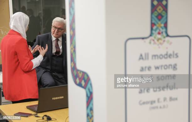 German president FrankWalter Steinmeier watches a researcher work during a visit at the King Hussein Business Park in Amman Jordan 28 January 2018...