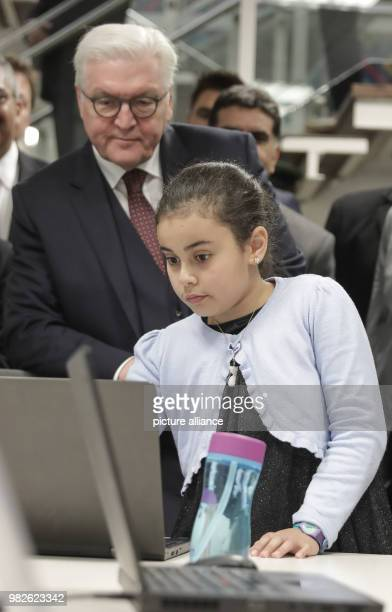 German president FrankWalter Steinmeier watches eight year old Nata work during a visit at the King Hussein Business Park in Amman Jordan 28 January...