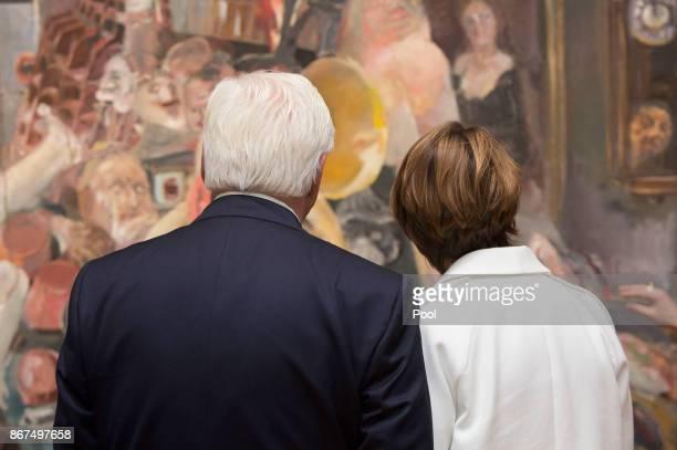 German President FrankWalter Steinmeier with his wife Elke Buedenbender look at the painting 'The Studio' by East German artist Bernhard Heisig...