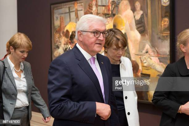 German President FrankWalter Steinmeier with his wife Elke Buedenbender walk past the painting 'The Studio' by East German artist Bernhard Heisig...