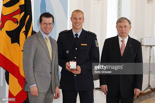 German President Horst Koehler and German Defense Minister KarlTheodor zu Guttenberg pose with bobsled driver David Moeller at the Silbernes...