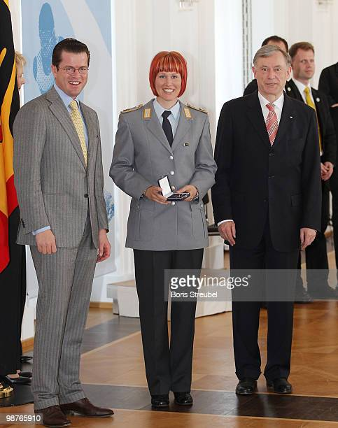 German President Horst Koehler and German Defense Minister KarlTheodor zu Guttenberg pose withGerman biathlete Kati Wilhelm at the Silbernes...