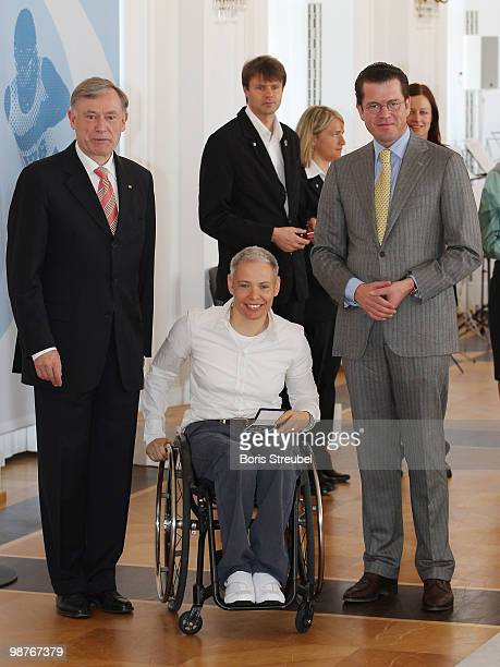 German President Horst Koehler and German Defense Minister KarlTheodor zu Guttenberg pose with the cross country skier Andrea Eskau at the Silbernes...