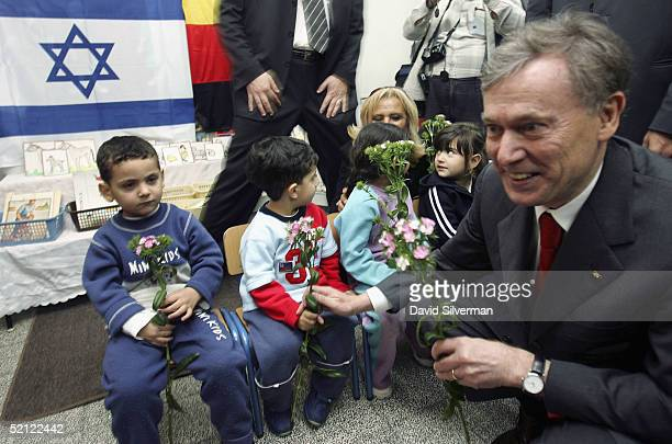 German President Horst Koehler distributes flowers to the children he received them from when they welcomed him at Lilach kindergarten on February 2...
