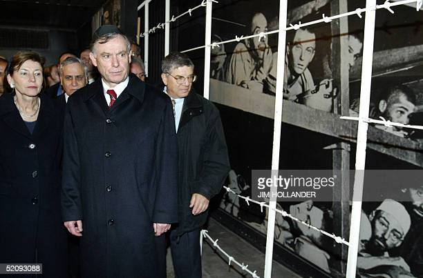 German President Horst Koehler flanked by his wife Eva and a guide to the Yad Vashem Holocaust Memorial passes a photo mural from a Nazi death camp...