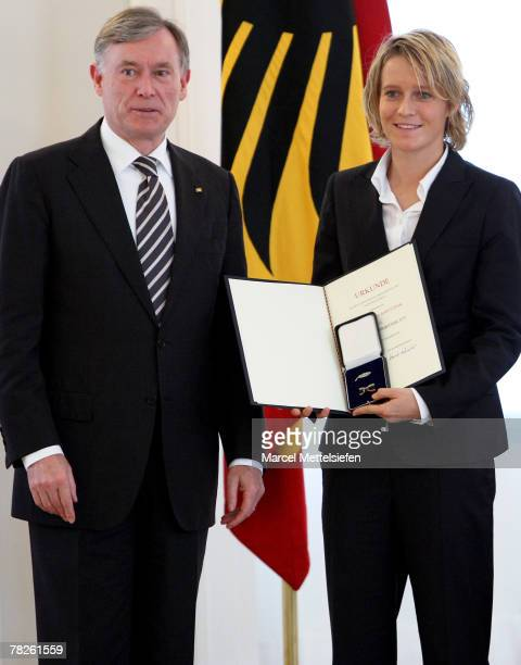 German President Horst Koehler hands over the Cross of Merit to Saskia Bartusiak of the Germany's women's national football team during the Silver...