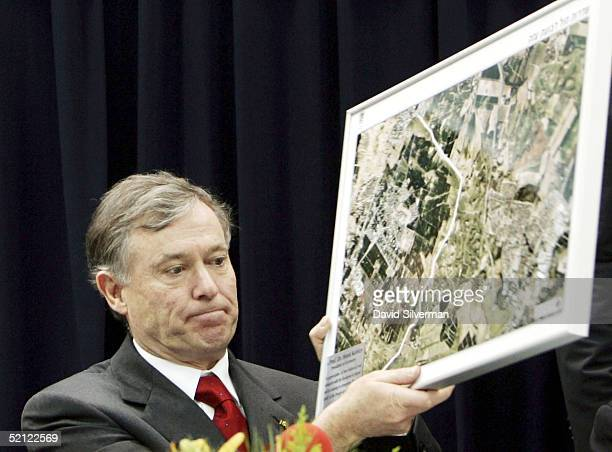 German President Horst Koehler holds an aerial photo showing the proximity of the Israeli town of Sderot with the neighboring Palestinian Gaza Strip...