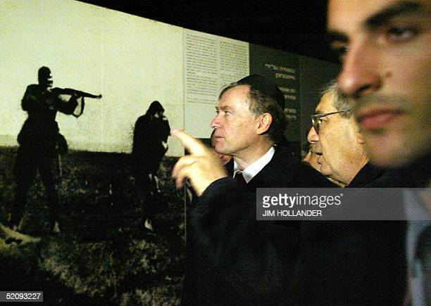German President Horst Koehler looks at a mural photo showing a Nazi soldier aiming a rifle at a Jewish woman as a guide talks during a tour of the...